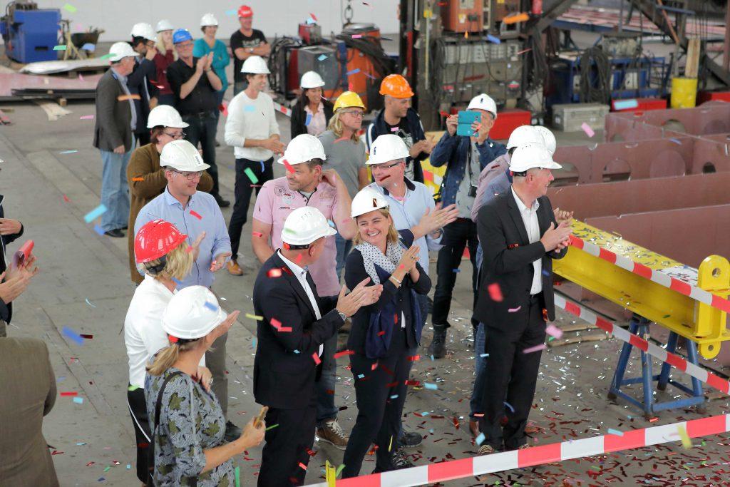 Mensen klappen bij feestelijke gebeurtenis in de hal van scheepswerf Bijlsma